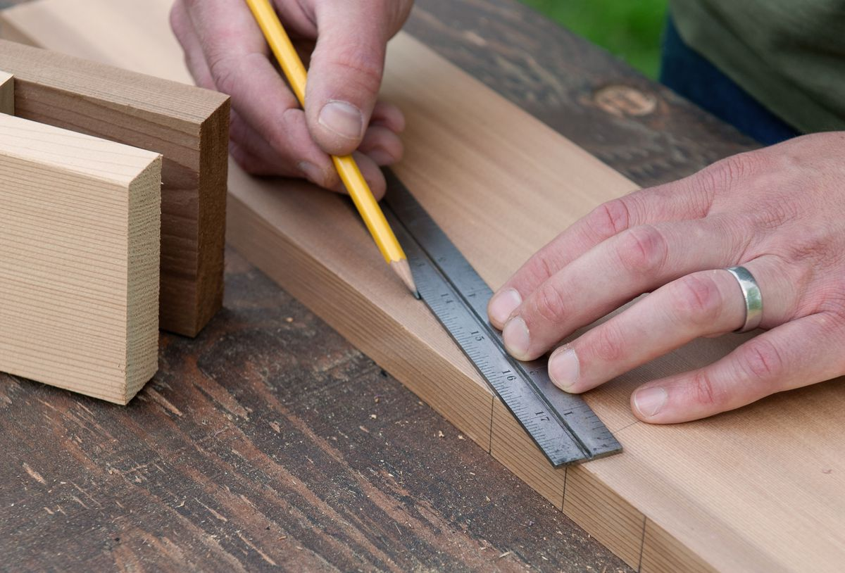 Man Lays Out Brackets And Feet Of Picnic Table