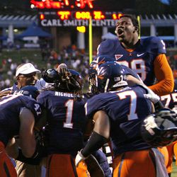 Virginia's Chris Brathwaite, top right, and other teammates celebrate their 21-20 overtime win over the Idaho in an NCAA college football game Saturday, Oct. 1, 2011, in Charlottesville, Va.