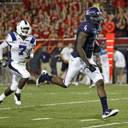 Arizona's Dan Buckner (4) runs the ball pass South Carolina State's Kimario McFadden (7) for a touchdown during the third quarter of an NCAA college football game at Arizona Stadium in Tucson, Ariz., Saturday, Sept. 15, 2012.