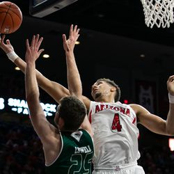 Arizona's Chase Jeter (4) reaches for a stray rebound past Utah Valley's Wyatt Lowell (25) during the Arizona-Utah Valley game in McKale Center on December 6 in Tucson, Ariz.