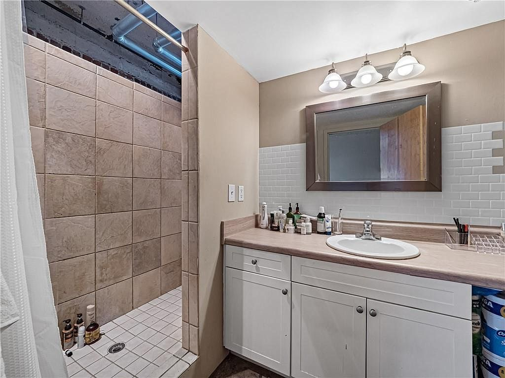A white and beige bathroom with a big shower.