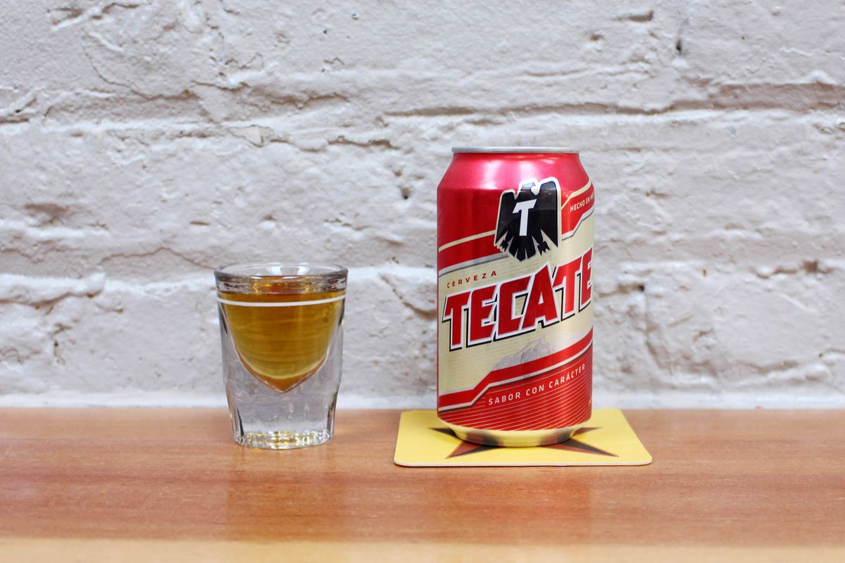 A shot glass filled with brown liquor and a red can of Tecate beer on a yellow Big Star coaster sit on a wood bar with a white brick wall behind them.