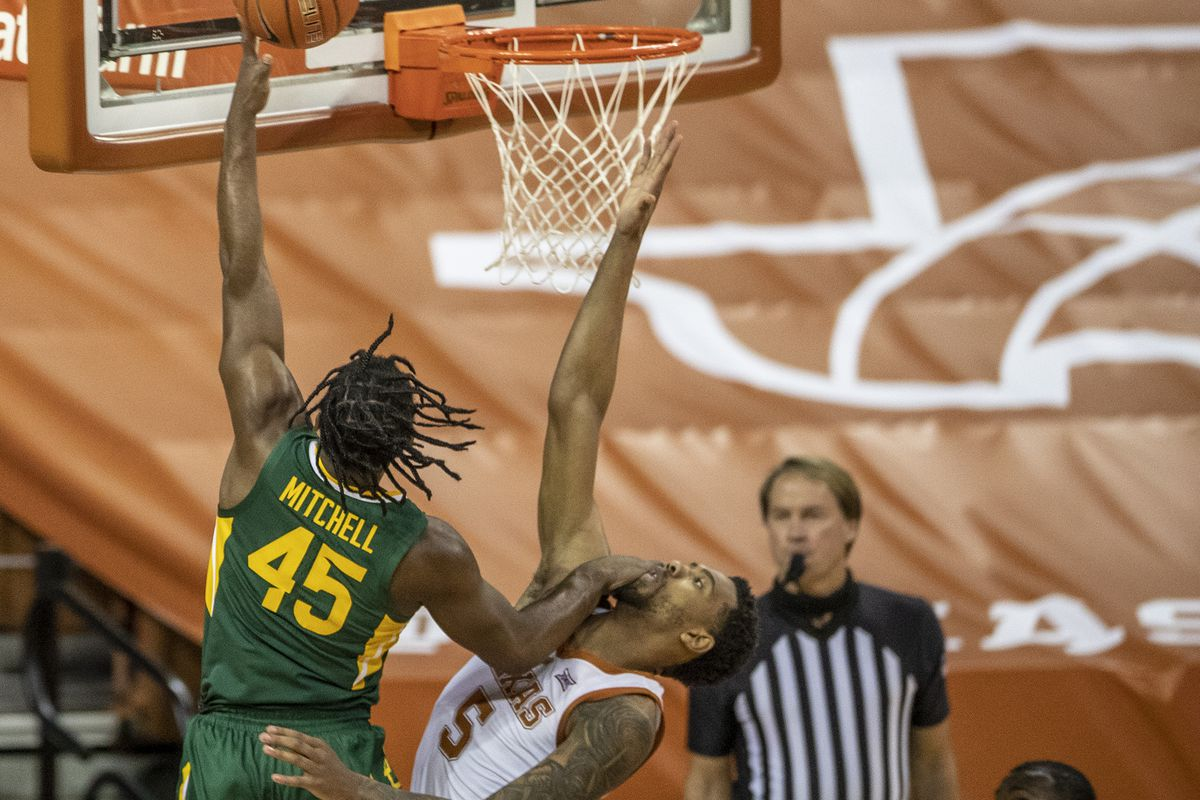 Davion Mitchell lays the ball in against Texas Longhorns forward Royce Hamm Jr. in the first half of an NCAA college basketball game at the Frank Erwin Center onTuesday, Feb. 2, 2021, in Austin, TX.