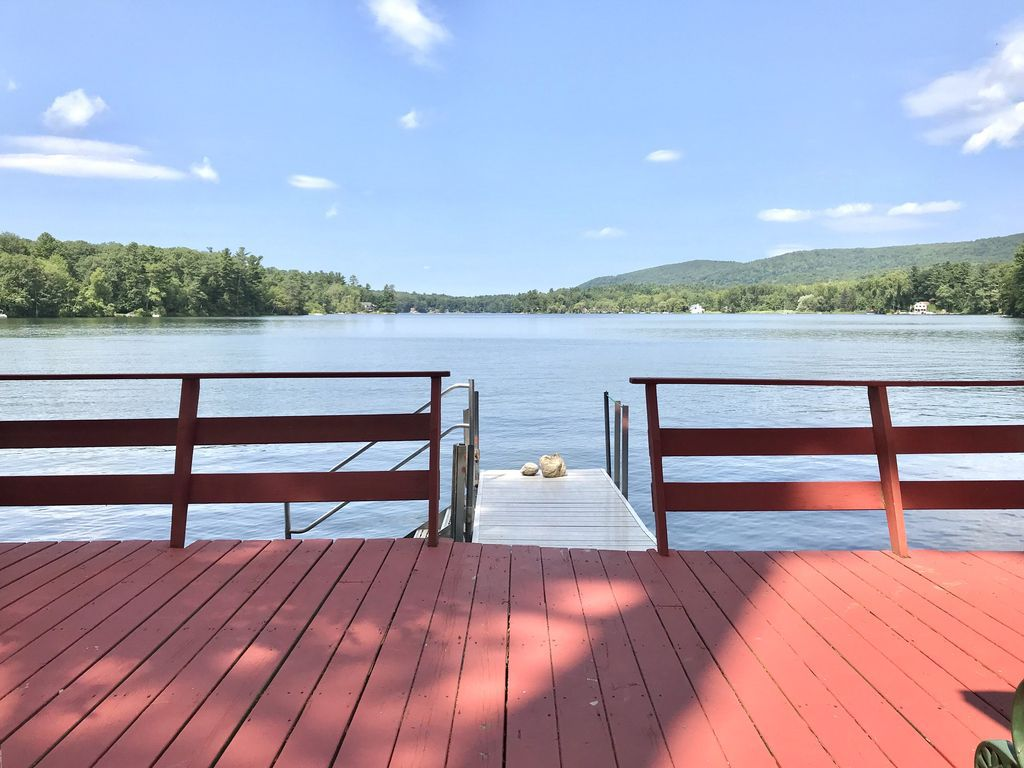 A deck with a short wharf off it leading to a lake on a sunny day.