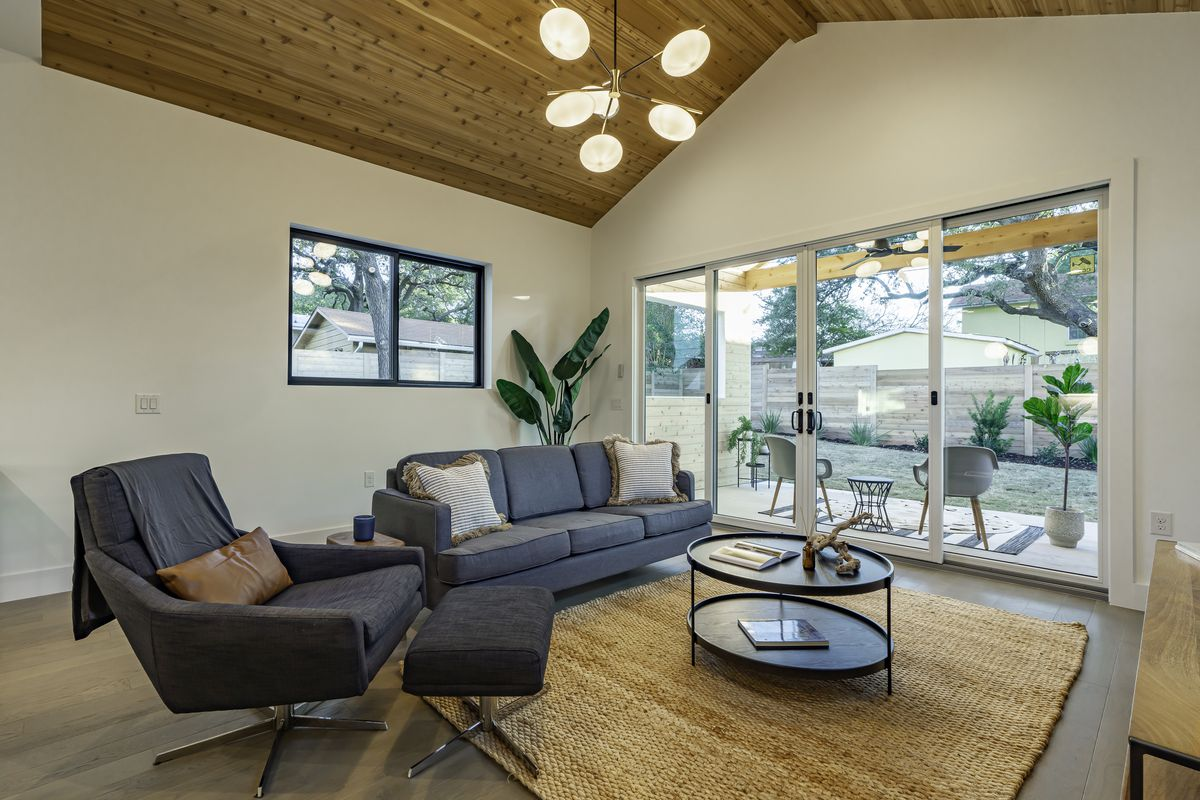 Photo of a living room of a new contemporary house. A modern couch and chairs are arranged on a fiber rug around a round two-tier coffee table. The room opens on to a porch through sliding glass doors.