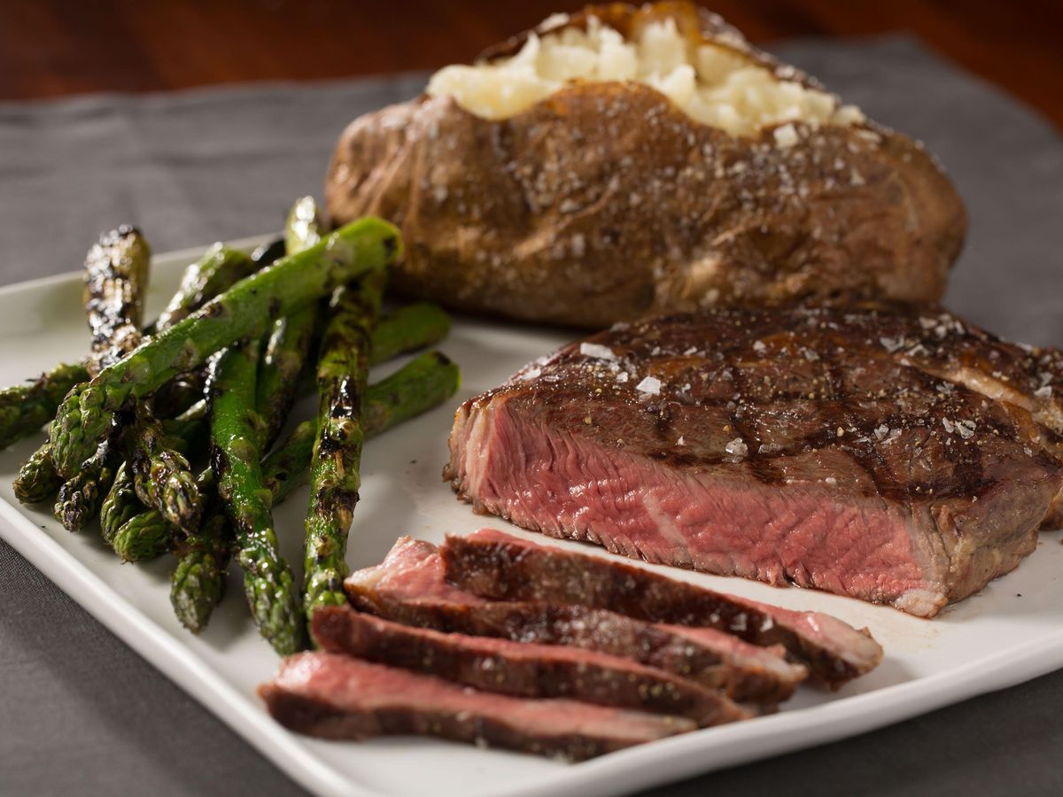Grilled steak with asparagus and a baked potato.