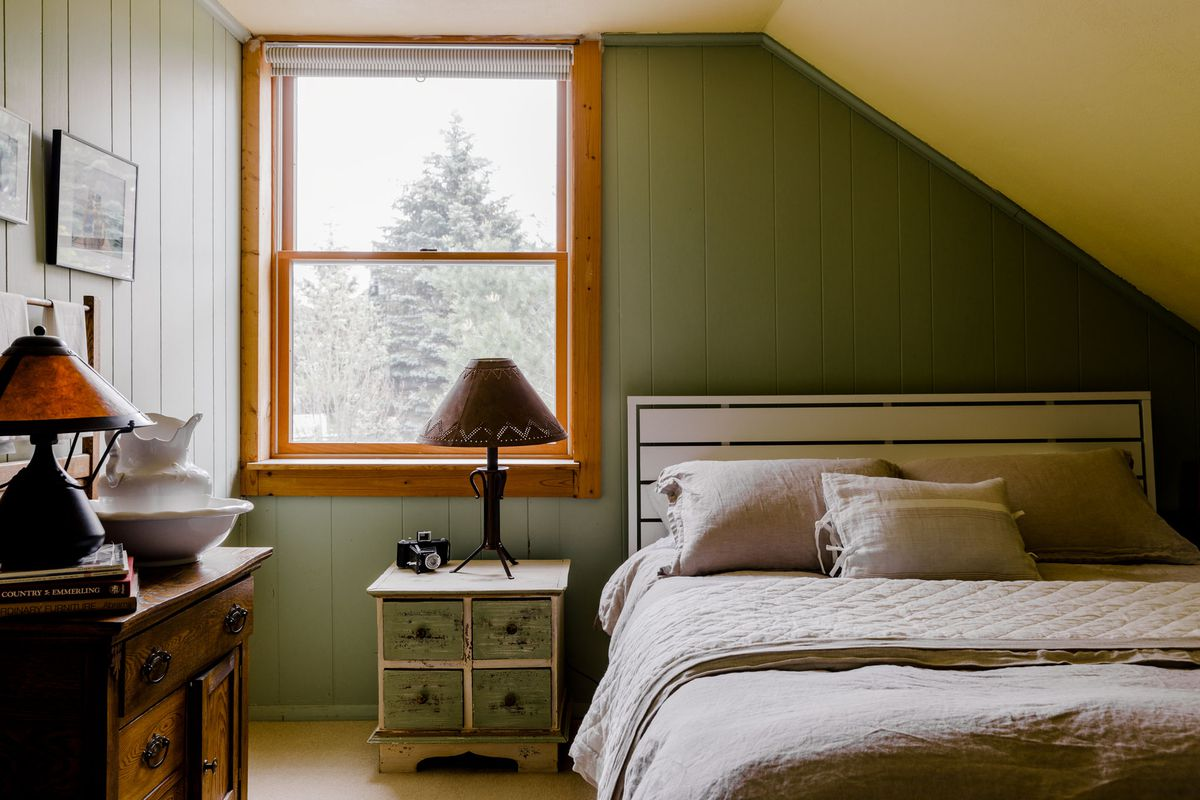 A bed with three pillows is in a bedroom with painted green walls, a nightstand with a lamp, and a table