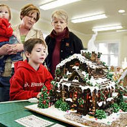 Six-year-old Coulson Harris, bottom, and his 1-year-old sister Catherine admire an ornate gingerbread house with their mother Kathy and grandma Letha at the Davis County Children's Justice Center. The house was donated for auction by Cheryl Fullmer.