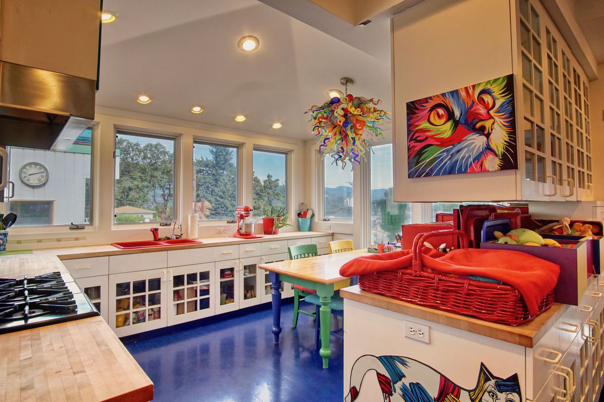 A kitchen has white cabinets, large windows, and bright blue floors.