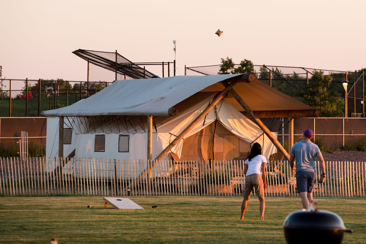 a couple playing cornhole in front of a glamping tent