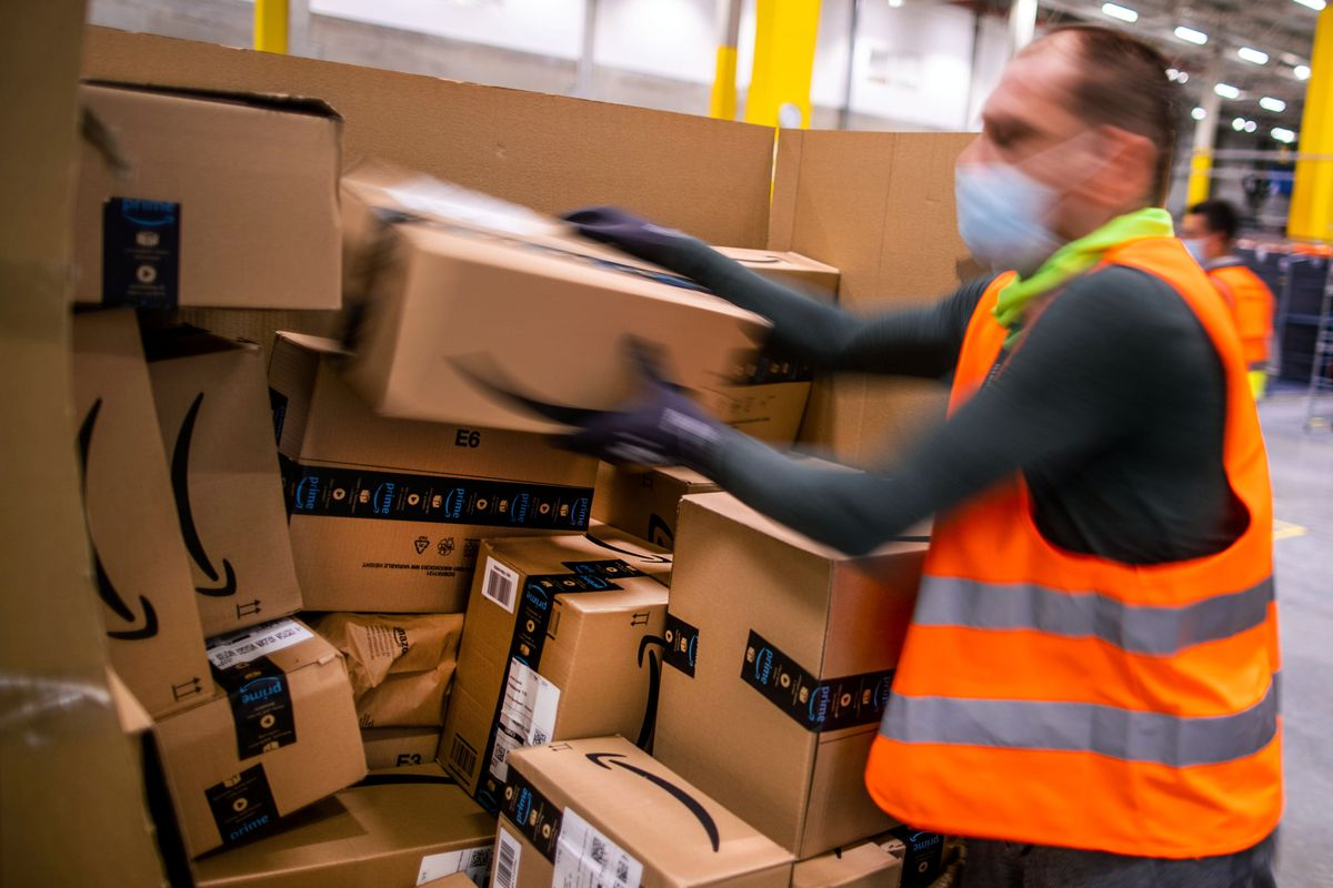 A warehouse employee, clad in an orange vest, sorts through a large pile of boxes in an Amazon distribution center, located in Germany.