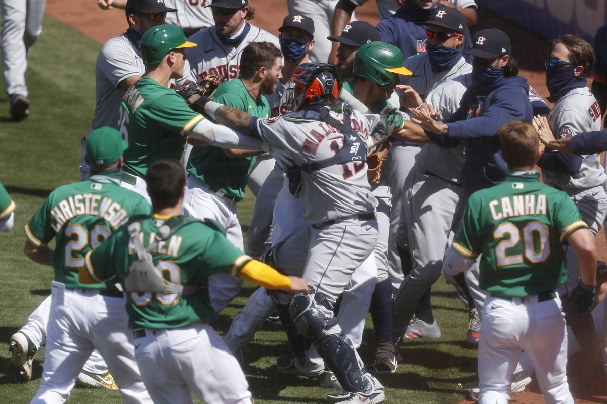 The Oakland Athletics and the Houston Astros benches scuffle after Athletics' Ramon Laureano charged Houston hitting coach Alex Cintron in the seventh inning at the Coliseum in Oakland, Calif., on Sunday, August 9, 2020.