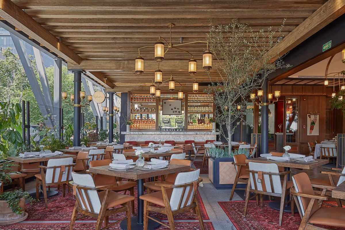 A lush wood and carpeted restaurant space seen from the side in daylight.