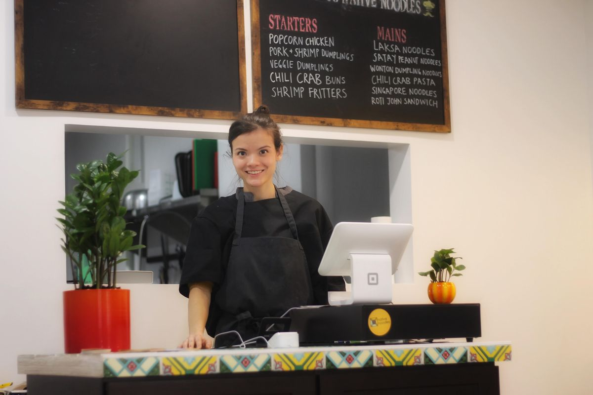 Amy Pryke, the owner of the restaurant Native Noodles, stands at the cash register at her restaurant