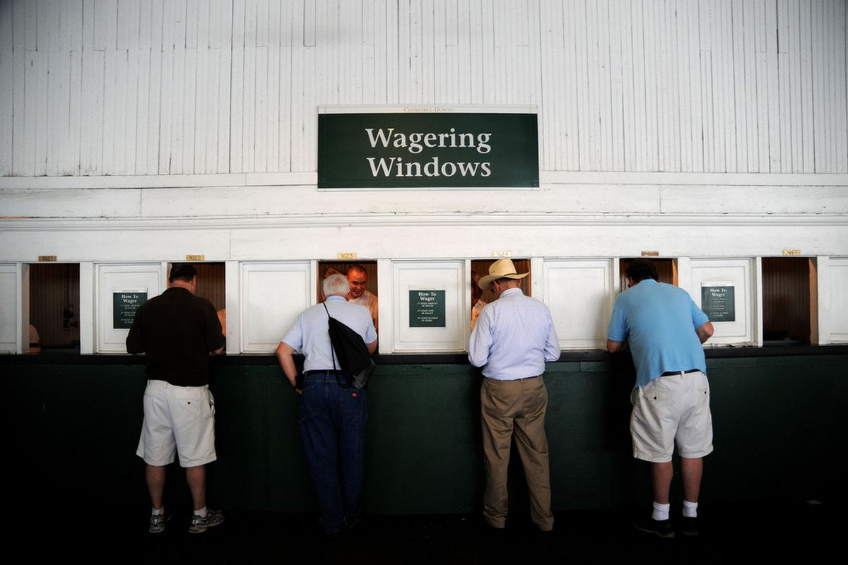 LOUISVILLE, KY - MAY 05:  Derby goers place bets at the wagering windows during the 138th running of the Kentucky Derby at Churchill Downs on May 5, 2012 in Louisville, Kentucky.  (Photo by Michael Heiman/Getty Images)