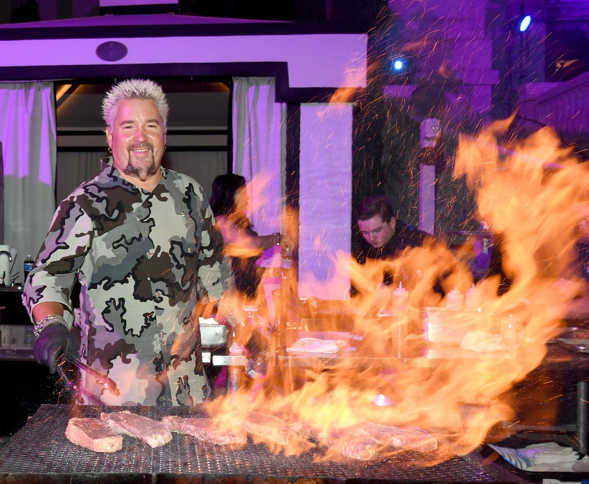 Guy Fieri grilling over a large fire