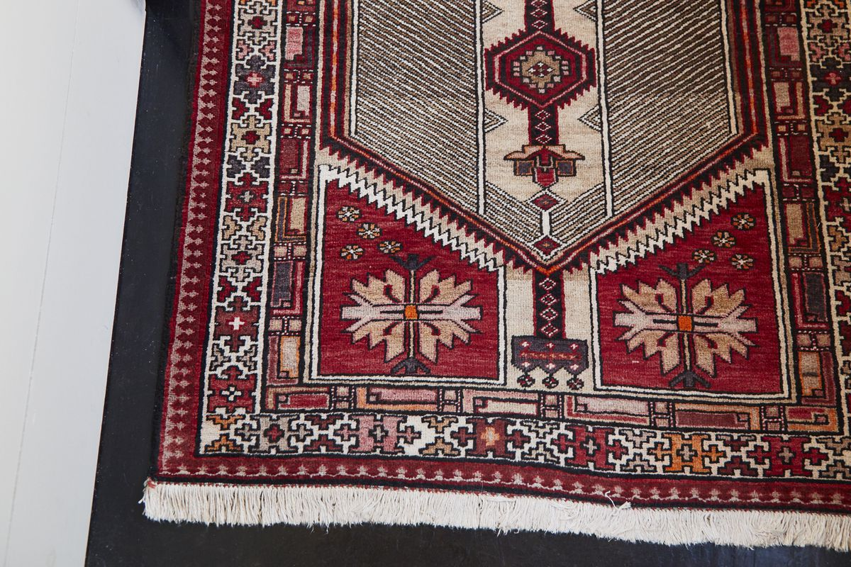 A detail of an antique rug shows an ornate pattern in rusty reds and creams.