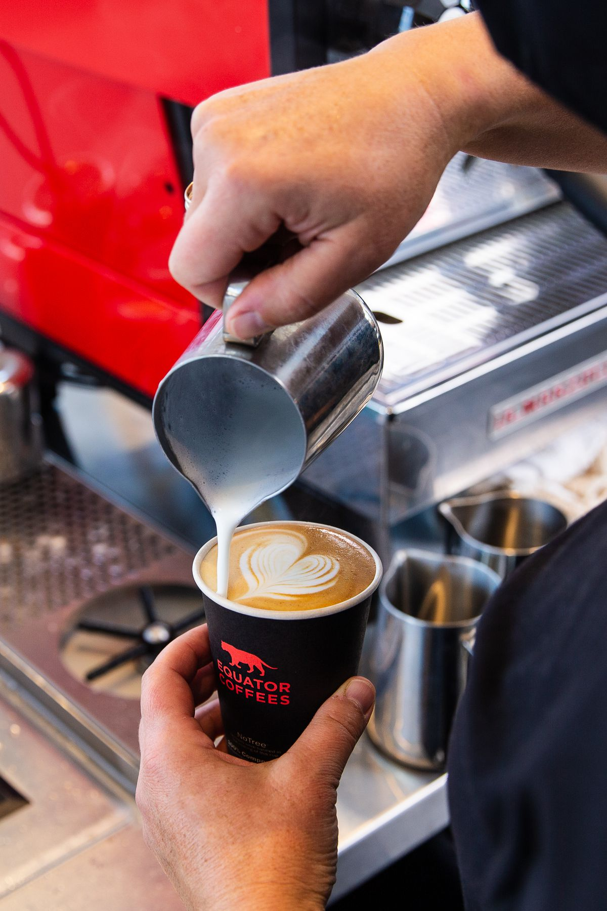 A latte being poured at Equator Coffees at Round House Cafe
