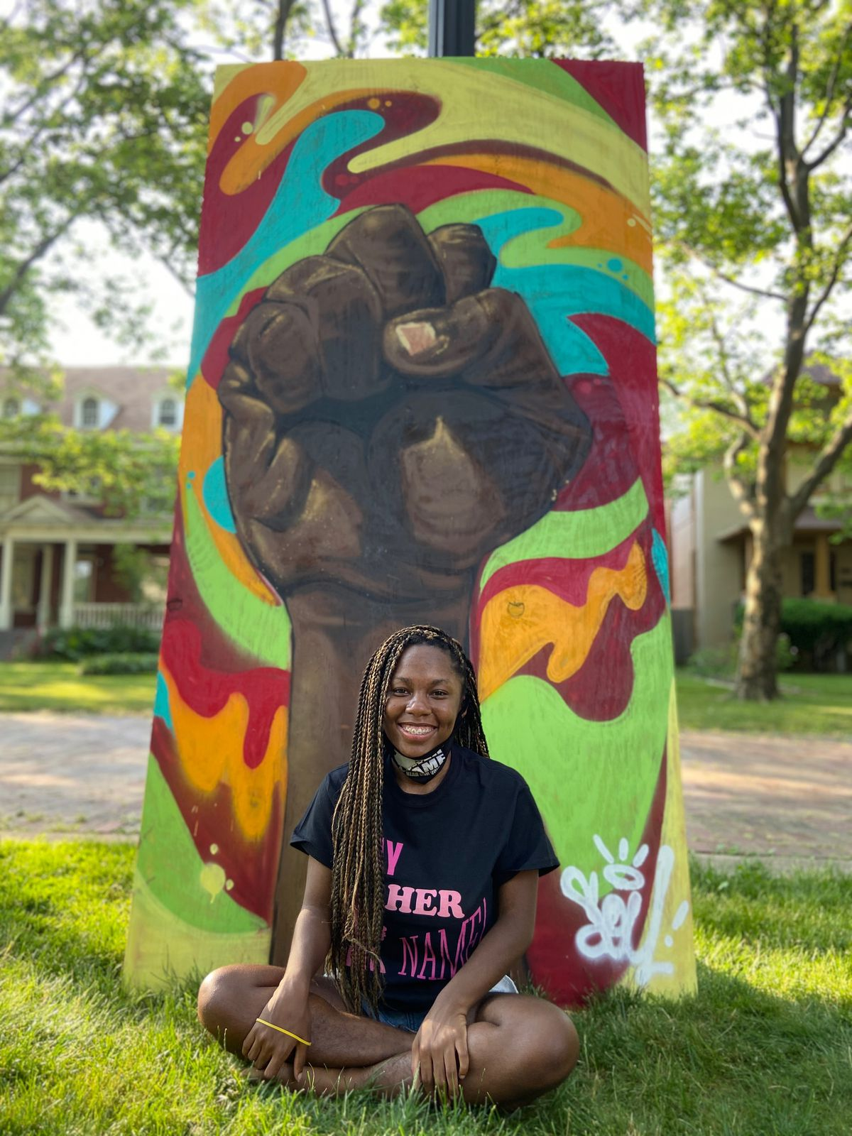 Detroit high schooler Ama Russell poses in front of a mural.