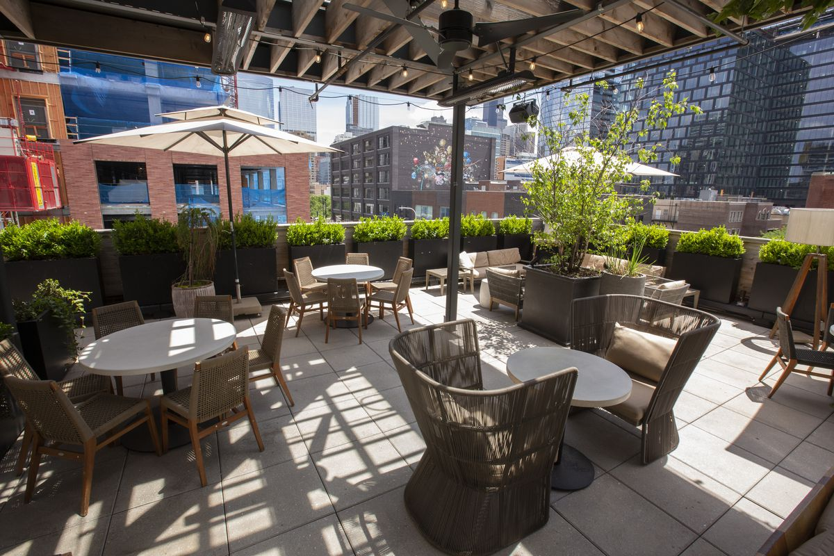A rooftop patio with tables and chairs