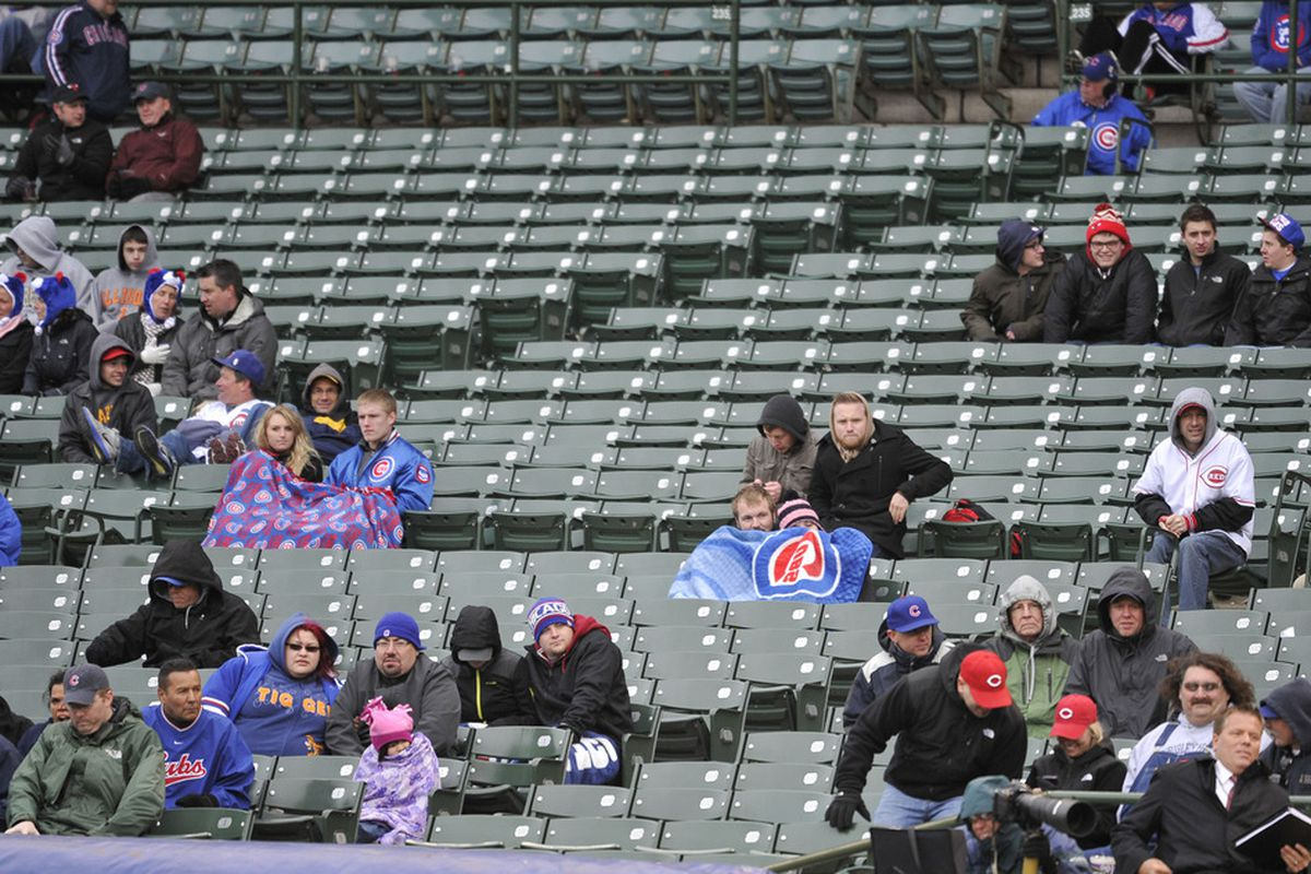 Fans brave cold temperatures and rain to watch the Chicago Cubs play the Cincinnati Reds at Wrigley Field in Chicago, Illinois. The Reds defeated the Cubs 9-4.  (Photo by Brian Kersey/Getty Images)