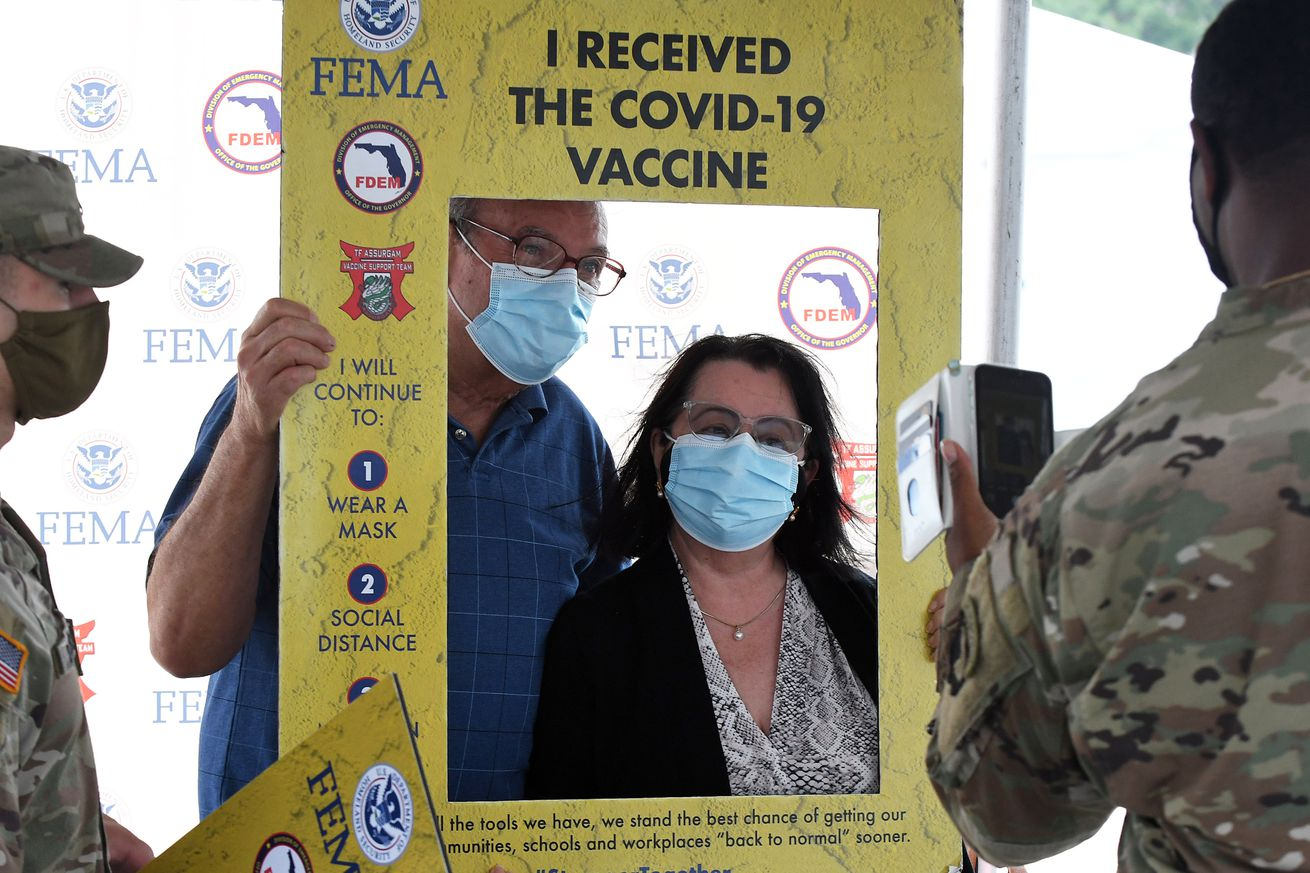 People pose for a photo after being vaccinated at the FEMA-...