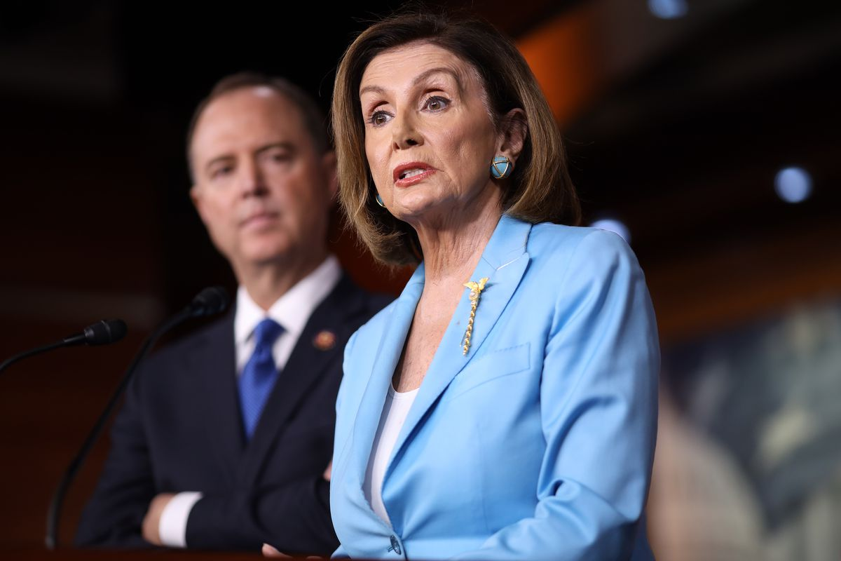 Speaker of the House Nancy Pelosi speaking to reporters with Representative Adam Schiff standing in the background.