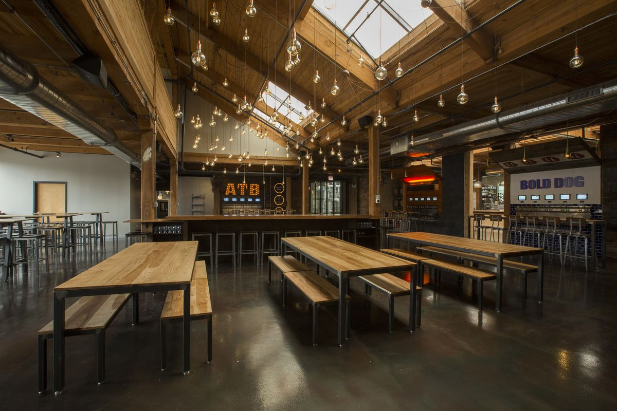 A brewery taproom with high ceiling, an industrial design, and benches.