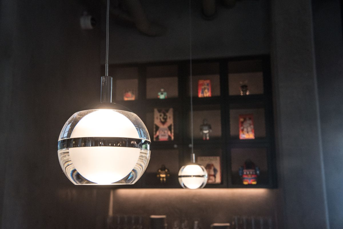 A closeup of two hanging lights with a display of Japanese robots in the background lit by the soft glow.