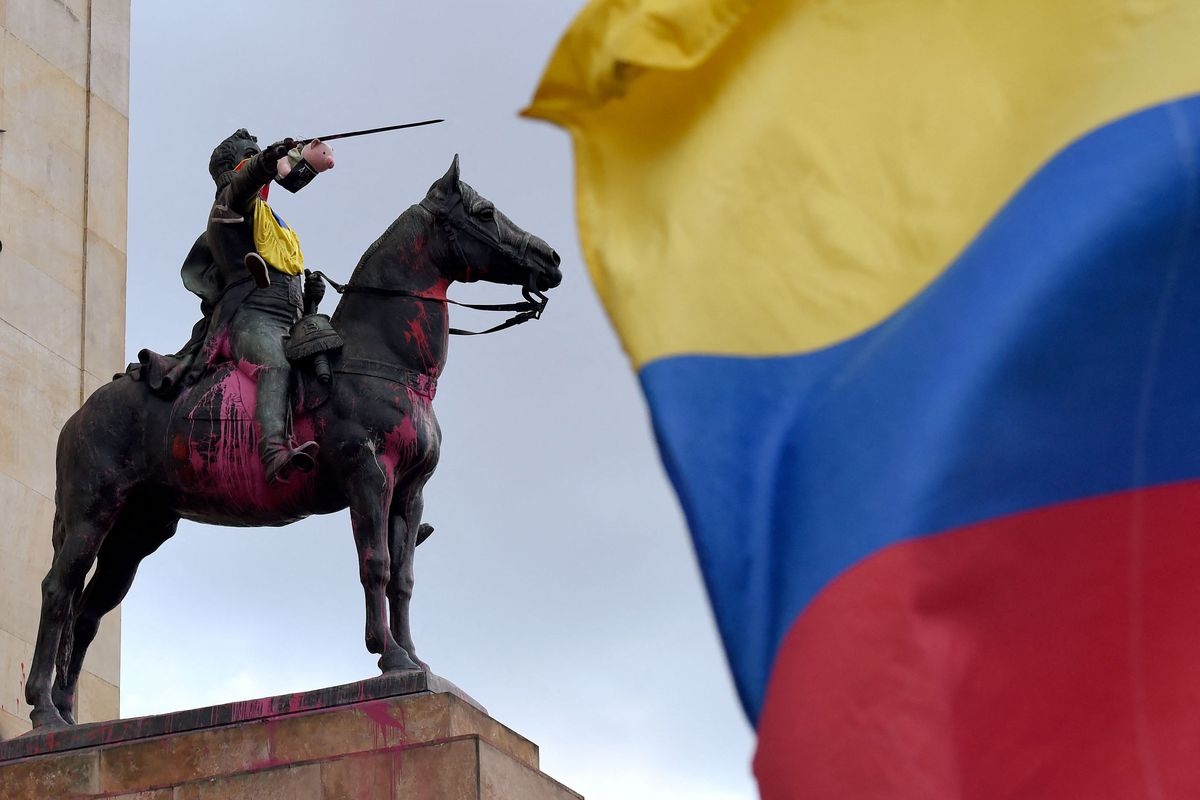 A pork toy representing Colombian President Ivan Duque is seen on the sword of a Colombian liberator Simon Bolivar's statue during the 10th consecutive day of protests against the government in Bogota on May 7, 2021.