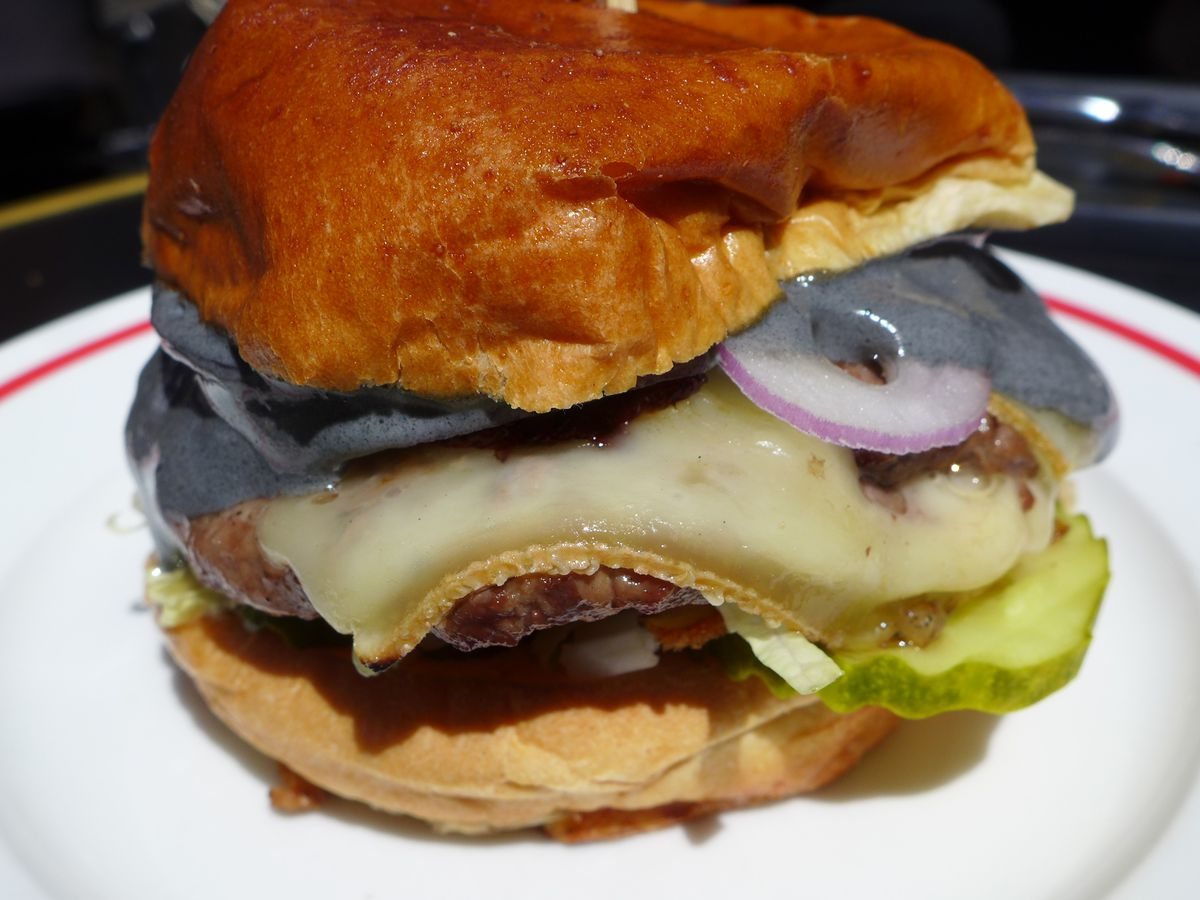A cheeseburger in brilliant sunlight on a plate with black sauce spilling out.