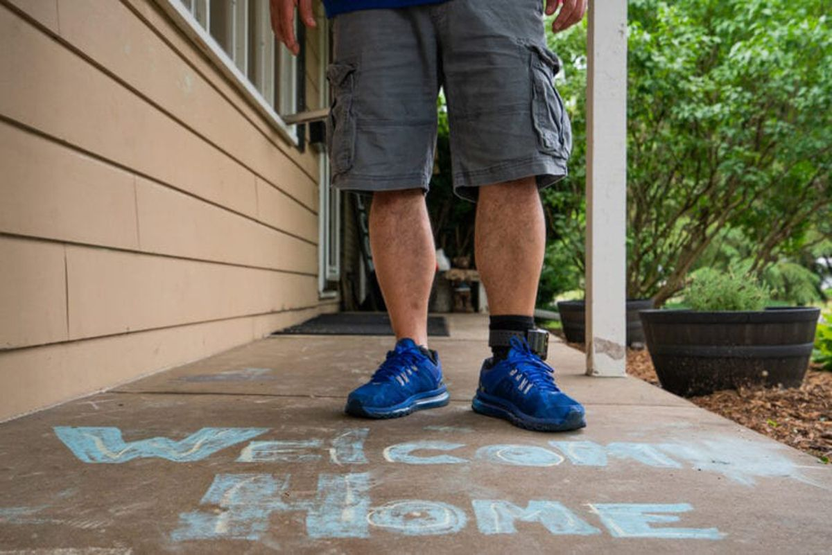 Cesar Elizarraraz stands with a welcome message on the front porch of his home in Crystal Lake. Though reunited with his family, his case is far from over.