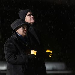 Mayor Lori Lightfoot (left) and first lady Amy Eshleman hold candles while looking out toward a darkened Chicago skyline during a national COVID-19 memorial, Tuesday, Jan. 19, 2021.