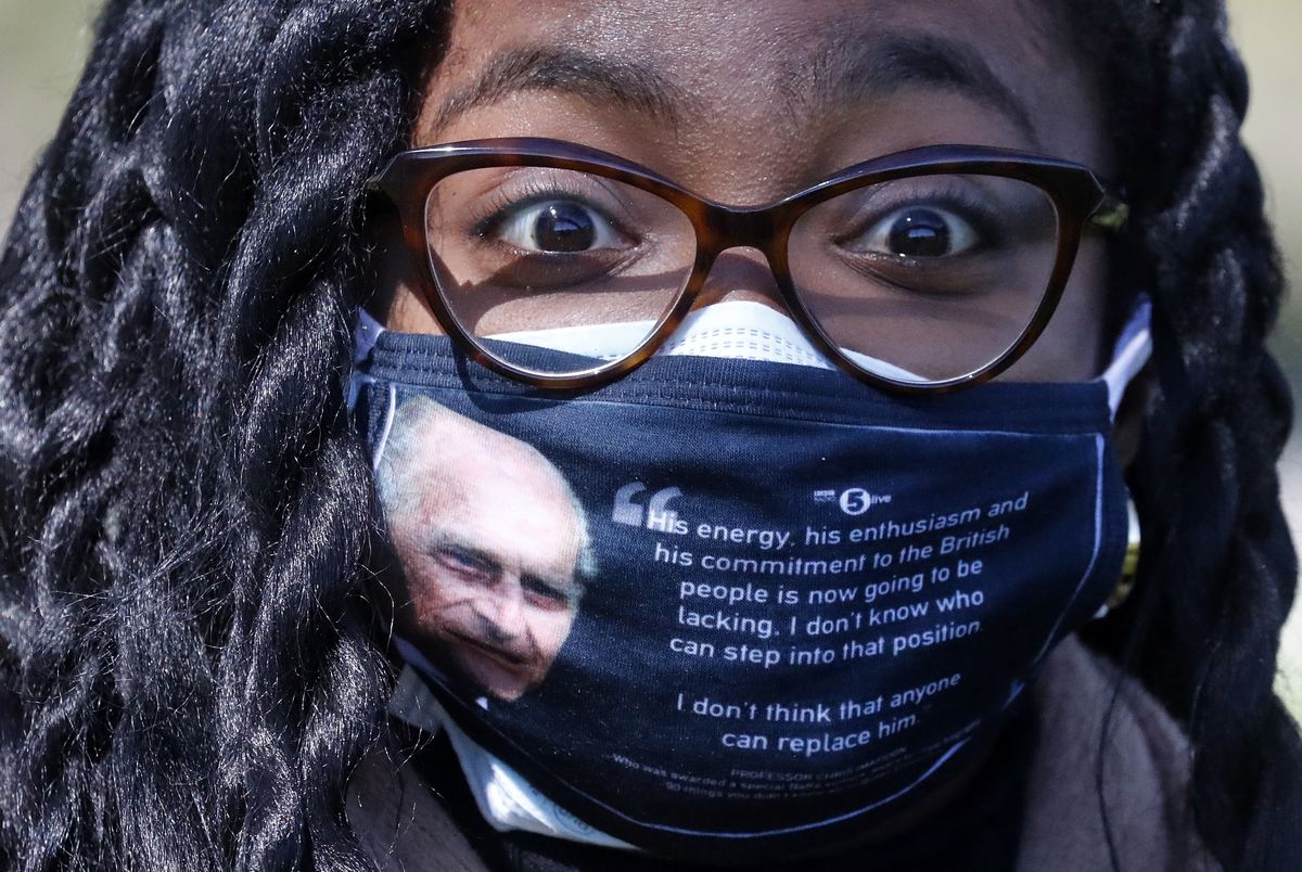 A woman wears a face covering with a picture of the Duke of Edinburgh as he walks along the Long Walk in Windsor on Saturday.