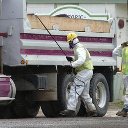 FILE - In this April 28, 2011 file photo, unidentified road workers wear protective gear against possible asbestos contamination as they load material from a road resurfacing project in downtown Libby, Mont. W.R. Grace, Inc., the chemical company blamed for polluting Libby, Mont. with asbestos dust that has killed hundreds of people, is pushing back against the Environmental Agency proposal and seeking to have it revised. Attorneys and scientists for W.R. Grace Inc., which operated an asbestos mine in Libby for three decades, say the EPA proposal would frustrate cleanup efforts by setting an unattainable standard for exposures.