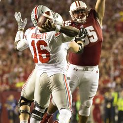 J.T. Barrett tries to throw by a Wisconsin defender.