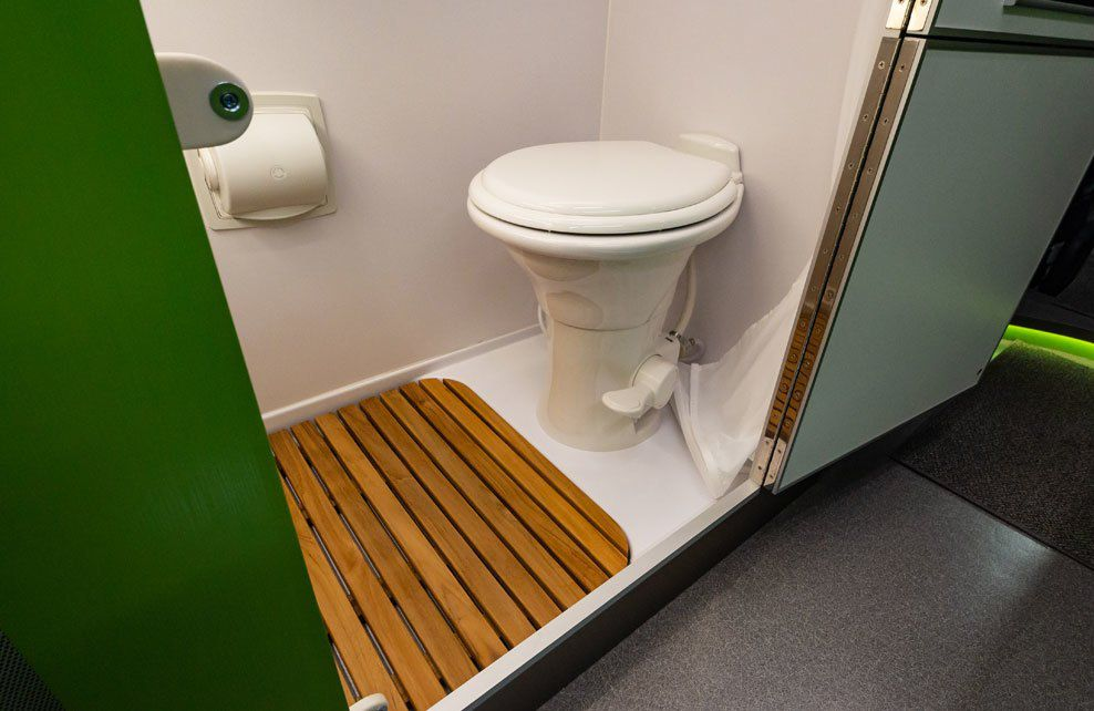 The camper's bathroom includes a white toilet, white walls, and a bamboo covering on the floor.