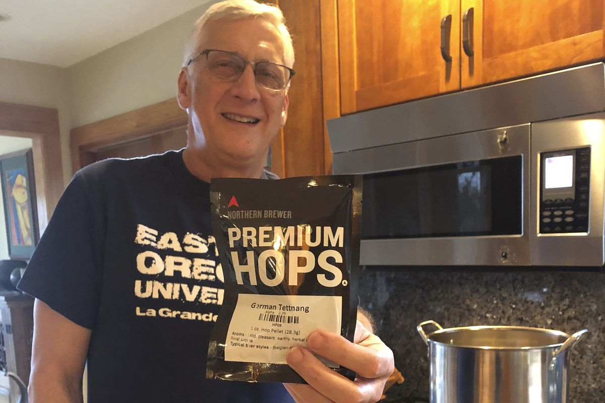 Andrew Selsky holds a bag of hops for home-brewed German-style hefeweizen. Homebrewing provides an escape from dwelling on the COVID-19 pandemic.