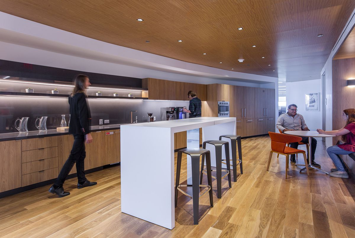 Contemporary office kitchenette, light wood floor, ceiling, cabinets, long white table with modern barstools in center. Four young to middle-aged white people variously walking making coffee, sitting at a round white table.