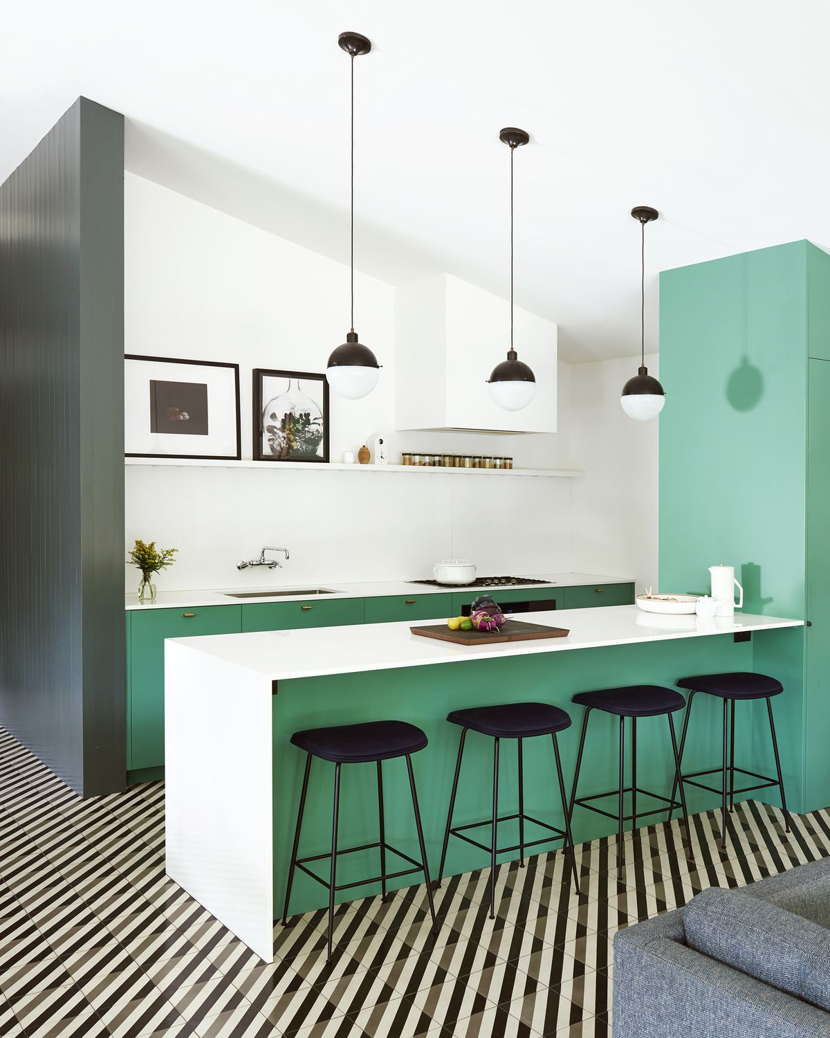 A sparse modern kitchen with clean lines and exposed shelving. There is a kitchen island with bright teal accent colors attached to a teal wall. Under the island sit four black stools. The floor is tiled with the same diagonally striped, black and white print that runs through the entire house.