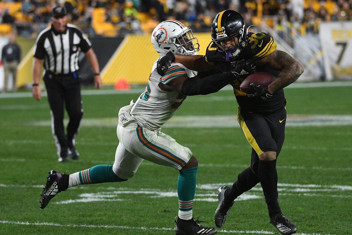 James Conner of the Pittsburgh Steelers carries the ball against Jerome Baker of the Miami Dolphins in the fourth quarter during the game at Heinz Field on October 28, 2019 in Pittsburgh, Pennsylvania.