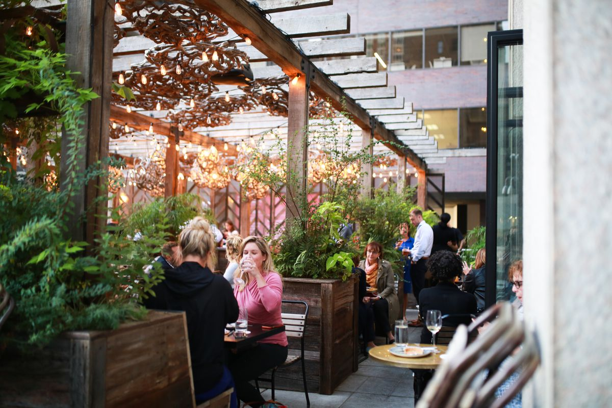 outdoor restaurant with people dining, plants, and hanging lights