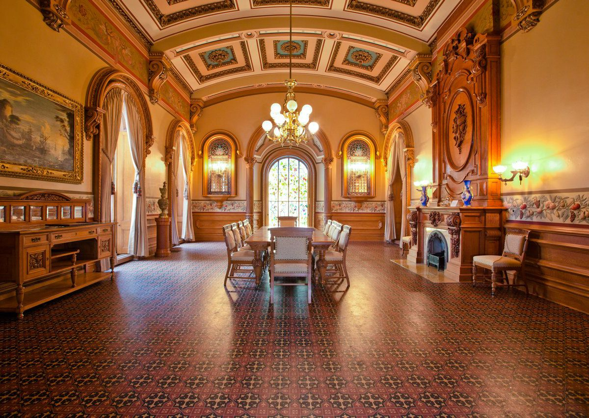 The interior of the Johnston Felton Hay House in Atlanta. The ceiling is inlaid, the floor has patterned tiles, and there are works of art on the walls. There is a chandelier hanging over a table with chairs.