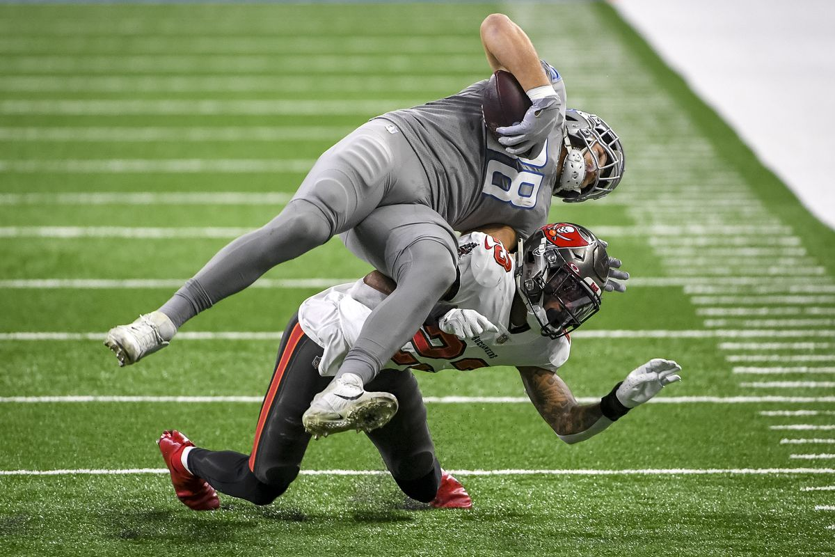 T.J. Hockenson #88 of the Detroit Lions is tackled by Sean Murphy-Bunting #23 of the Tampa Bay Buccaneers during the second half of a game at Ford Field on December 26, 2020 in Detroit, Michigan.