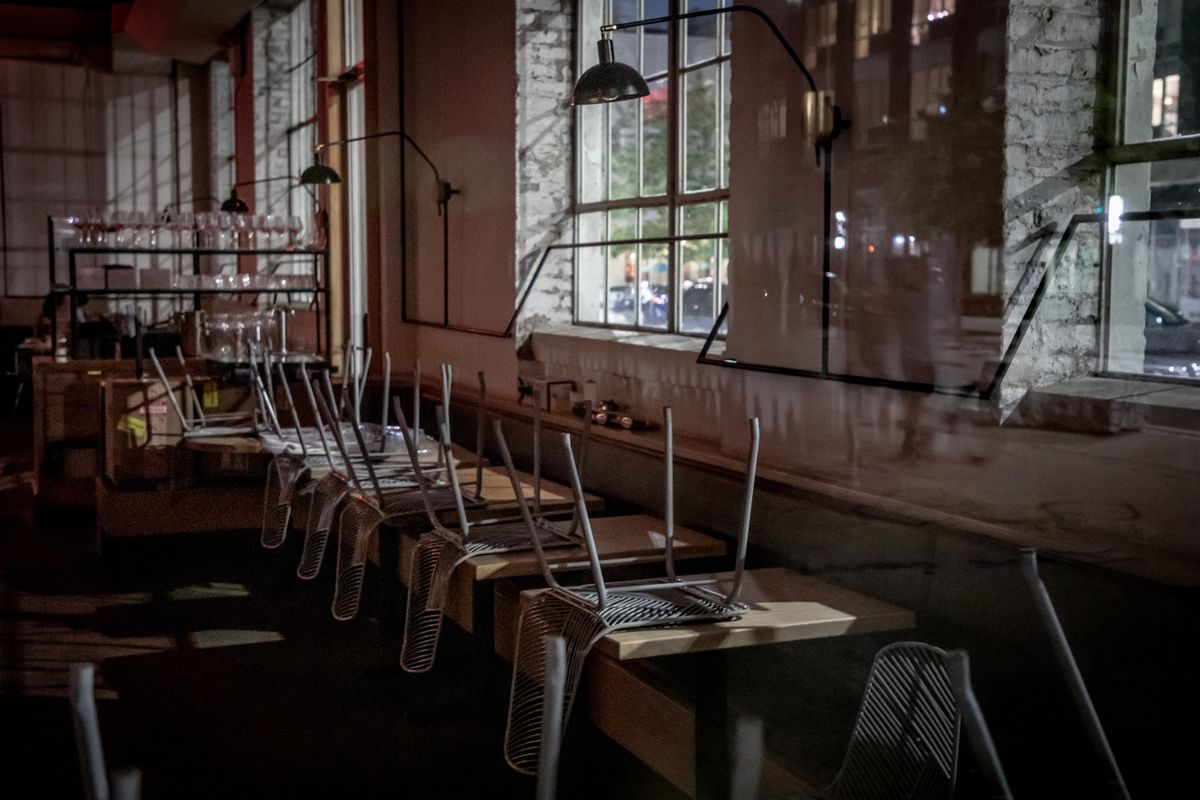 Inside an empty restaurant with seats turned up and placed on tables