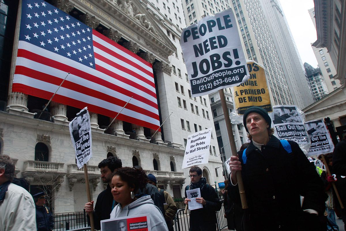 """Protesters demonstrating against Wall Street bailouts, one holding a sign reading, """"People need jobs."""""""