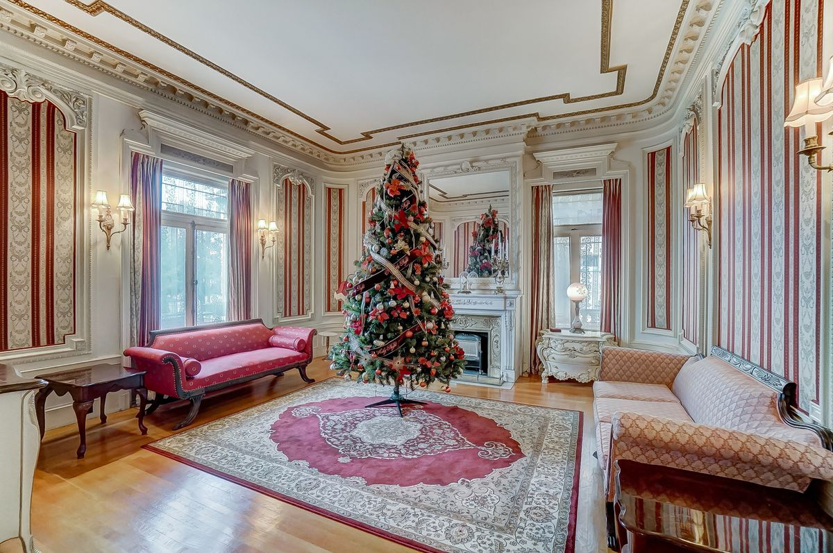 A formal sitting room has a christmas tree on a rug, crown moldings, a fireplace, and striped wallpaper.