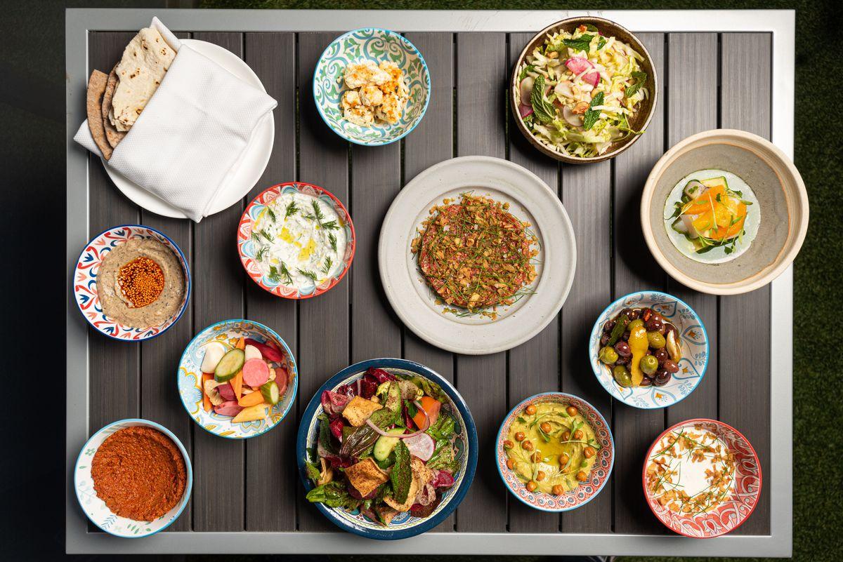 An overhead shot of mezze bowls and plates like pita.