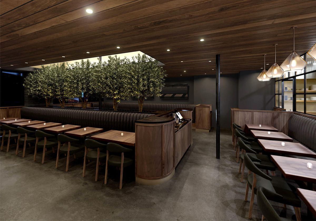 A rendering for a dark steakhouse with greens and low light and tables.