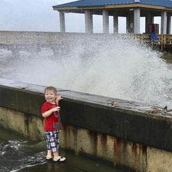 Jordan Fortune, 3, laughs as a wave churned up by Tropical Depression Cindy  hits a sea wall at the harbor in Pass Christian, Miss., on Thursday, June 22, 2017.